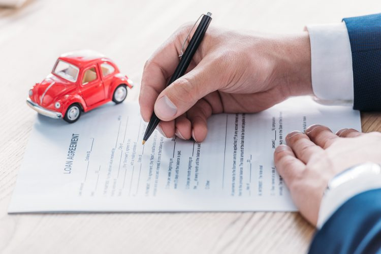 view of car dealer writing in loan agreement